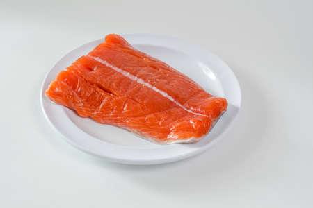 Raw wild king Salmon Fillet lying on white place, against white background Stock Photo