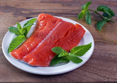 Raw wild king Salmon Fillet lying on white place, on wooden background, decorated with mint leaves
