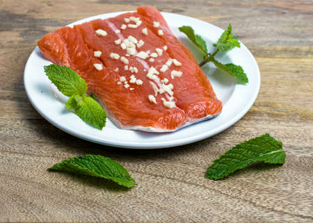 Raw wild king Salmon Fillet lying on white place, on wooden background, decorated with mint leaves and garlic marinate