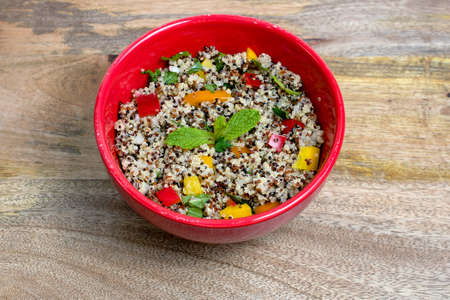Closeup on red bowl with tri-color vegan quinoa salad on wooden background - quinoa is a pseudograin that has all nine essential amino-acids