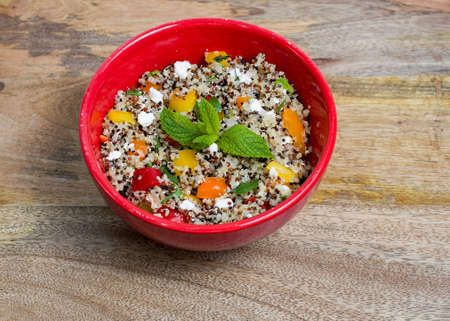 Closeup on red bowl with tri-color quinoa salad on wooden background - quinoa is a pseudograin that has all nine essential amino-acids