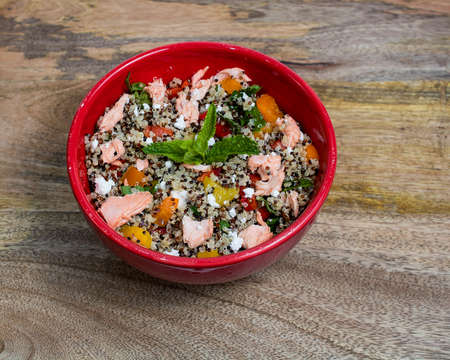 Closeup on red bowl with tri-color quinoa salad on wooden background - quinoa is a pseudograin that has all nine essential amino-acids -  Stock Photo