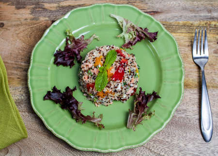 Closeup on green plate with tri-color quinoa salad on wooden table, and a fork - quinoa is a pseudograin that has all nine essential amino-acids  Stock Photo