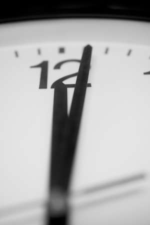 Closeup and selective on the pointers of a clock marking a minute after midnight - black and white rendering. The main focus is on the number twelve and its pointer. Stock Photo