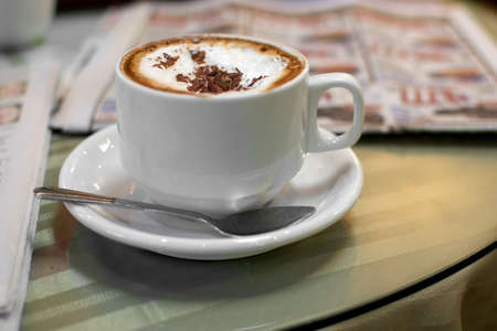 Selective focus on cappuccino on table at a cafe, surrounded by newspapers - coffee time the old way