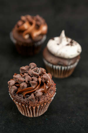Three chocolate cupcakes garnished with chocolate chips and whipped cream frosting on lined up across the frame, on black background Stock Photo
