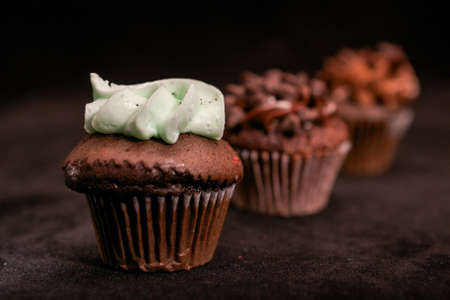 Three chocolate cupcakes garnished with chocolate chips and chocolate and mint frosting on lined up across the frame, on black background Stock Photo