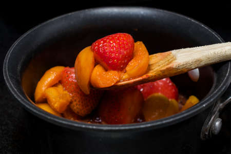 Wat abrikoos en aardbeigelei oprapen in een pan met antiaanbaklaag op een fornuis