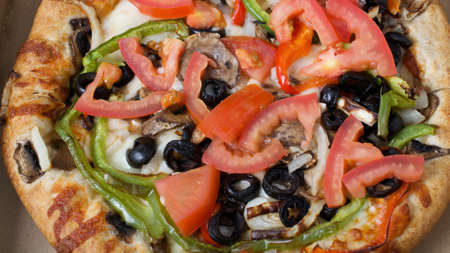 Closeup on vegetarian pizza with  tomatoes, black olives, mushrooms, onions, green peppers and mozzarella