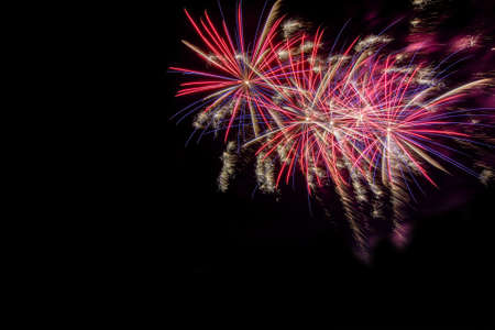 Bursting fireworks against black background celebrating an important event like new years eve or US independence day with copyspace