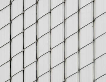 White pattern of vertically oriented chain-linked fence covered with plastic -texture or background