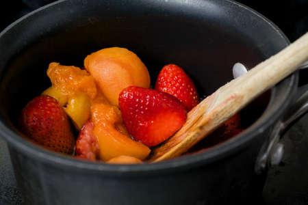 Abrikoos en aardbeiengelei maken in een antikleefpan op een fornuis