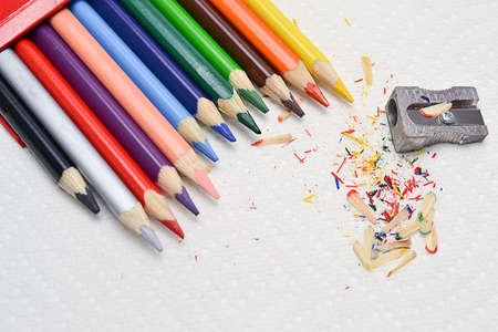 Closeup on drawing colorful pencils and sharpener on a white paper towel  Stock Photo