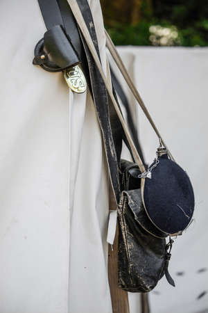 Canteen, leather backpack, leather belt and US badge hanging at the entrance of a civil war era reenactment tent