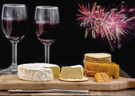 Brie and hot pepper jack cheese on wooden cheese board, accompanied by crackers and two glasses of red wine, against black background decorated with colorful fireworks