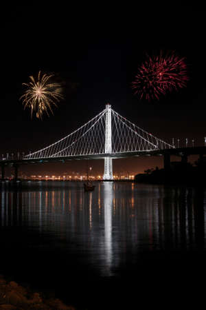 New East Span Bay Bridge illuminated  at night, reflecting color lights. Iconic and majestic bridge after dark viewed from Treasure Island in San Francisco. Stock Photo
