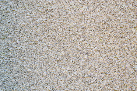Old worn out tan stucco cement wall- texture or background Stock Photo