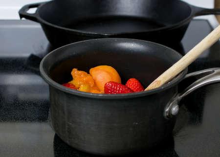 Het maken van abrikozen en aardbeiengelei in een antikleefpan boven op een elektrisch fornuis Stockfoto