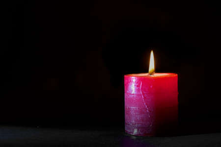 One orange red candle lit against black background Stock Photo