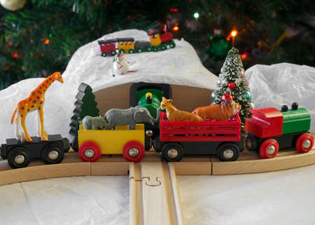 Christmas display featuring generic wooden train set, plastic, African animal toys, fake snow and a Christmas tree in the background- eclectic Christmas display concept