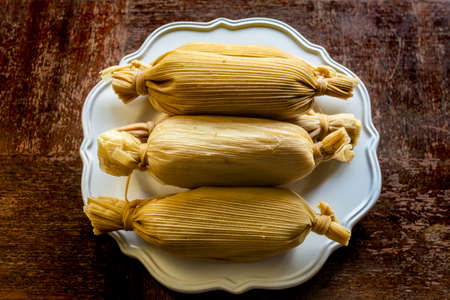 Unwrapped stacked Mexican tamales in white plate on grunge wooden table viewed from above - ethnic Food concept
