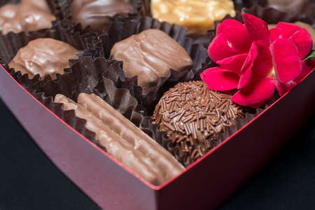 Closeup on the bottom of heart-shaped box filled with chocolate candies on black background, decorated with red flower- passion and love concept 写真素材
