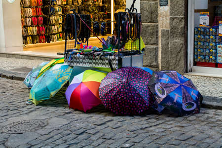 RIO DE JANEIRO, RJ , BRAZIL - May 22, 2018:  Street vendors on the streets of downtown Rio selling umbrellas, belts and other good in front of stores. Street vendors known as camelos are part of Brazil's informal economy