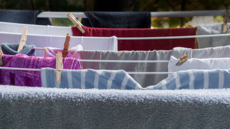 Old cloths drying out on metal clothesline in a backyard, viewed from above. Hanging clothes saves energy and is more ecological than using a dryer