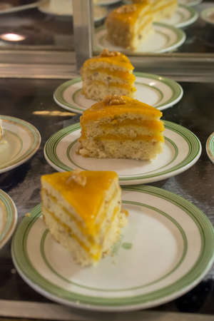 Passion fruit (Maracuja) cake, a tasty Brazilian dessert made viewed through the glass of a bakery Imagens