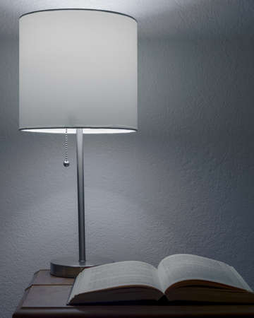 An old open book, underneath a bedside table lamp, against white wall, suggestinga break from reading