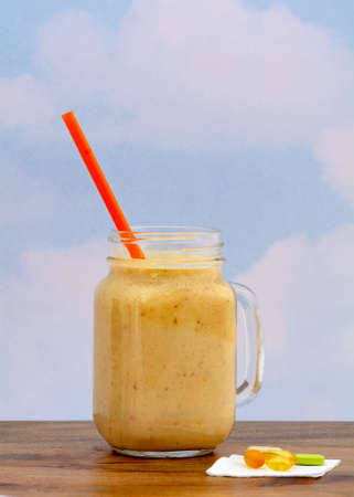 Peach smoothie in glass mug served with orange straw against blue sky background on wooden table, and dietary supplements