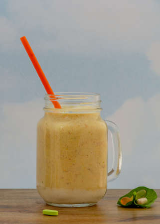 Peach smoothie in glass mug served with orange straw against blue sky background on wooden table, and dietary supplements inside spinach leaf