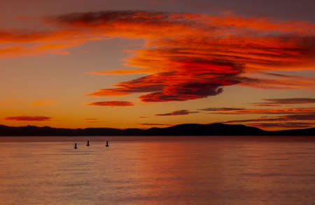 Sunset from South Lake Tahoe beach in California, USA, in the summer, featuring wild clouds and very colorful orange sky