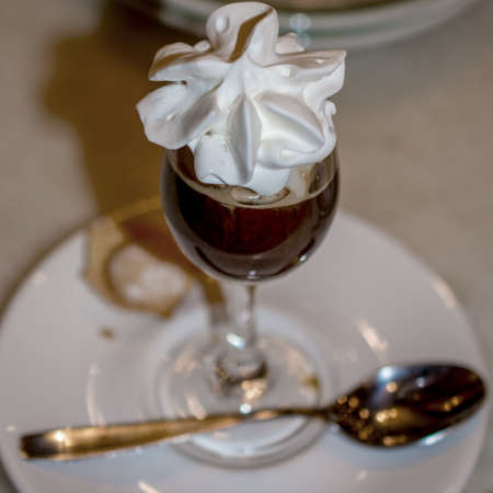 Irish coffee with whipped cream on top on white plate decorated with a spoon on a restaurant setting, dinner angle view Banco de Imagens
