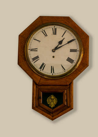 Eight corners wooden vintage clock on tan wall - octagon