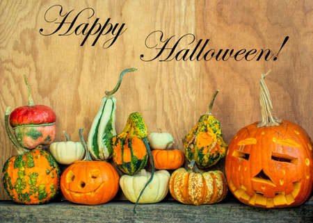 Happy Halloween copy space with carved pumpkins and gourds at the bottom against wooden background in side view