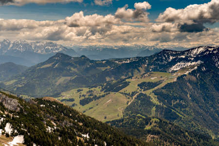 View from top of Mount Wendelstein in Upper Bavaria in the late Spring, featuring the Alps, pastures and fields at a distance