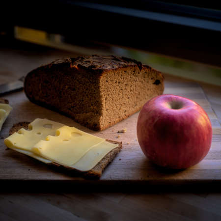Swiss cheese, apple and rye bread on wooden plate by a window  on dark background still life - simple meal concept