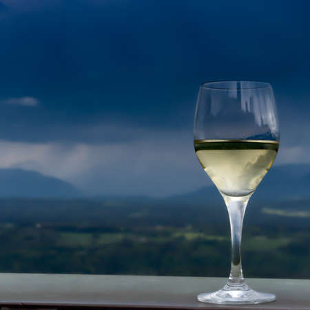 Selective focus on a drink of white wine on a counter overseing mountains in the background and approaching rain, with plenty of copy space  viewed from the side Stock Photo