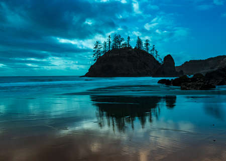 Long exposure, Grandmother Rock, Trinidad State Beach in Triidad, in the blue hour, in Northern California, USA, l featuring predominantly blue colors and some clouds, the blue colors intensified with a lens blue filter