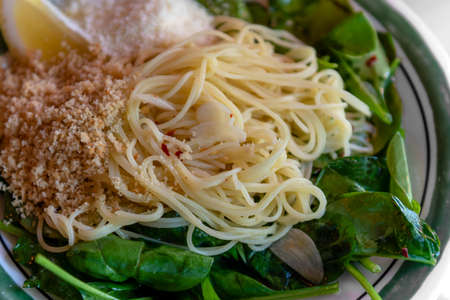 Close-up on capellini angel hair pasta with virgin olive oil, spinach, fresh lemon, chili flakes, garlic and  toasted bread crumbs, dinner angle view