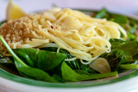 Close-up on capellini angel hair pasta with virgin olive oil, spinach, fresh lemon, chili flakes, garlic and  toasted bread crumbs, side view Stok Fotoğraf