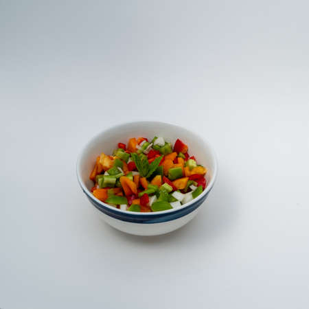 Close up on colorful peppers salad decorated with mint in bowl isolated in white  - dinner angle view