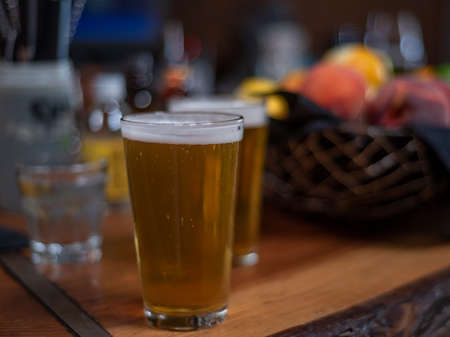 Selective focus on two glasses of beer viewed from the side in resturant setting, on wooden table,  next to a defocused fruit basket