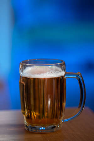 One glass of beer viewed from the side on a wooden table agasint blue background and lots of copy space