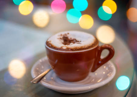 Brown cup of cappuccino on white Saucer with colorful bokeh balls with copy space, side view