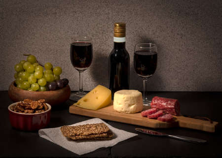 Brie and swiss cheese on black stone cheese board, accompanied by fruit, nuts, crackers and two glasses of red wine, against light color background Stok Fotoğraf