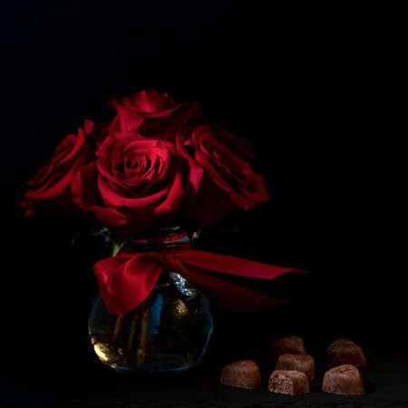 Beautiful red flowers bouquet and chocolates, in a glass vase, on dark bakground,  viewed from the side, happy valentines day