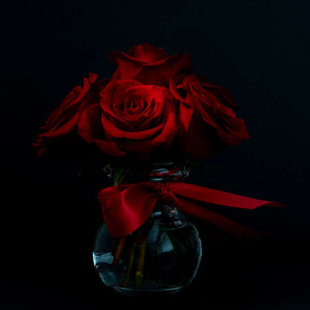 Beautiful and red flower bouquet, in a glass vase, on dark bakground,  viewed from the side, happy valentines day Stok Fotoğraf