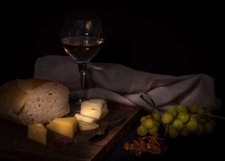 Brie and swiss cheese onwooden cheese board, accompanied by fruit, nuts, crackers and one glass of white wine, against black color background Stok Fotoğraf